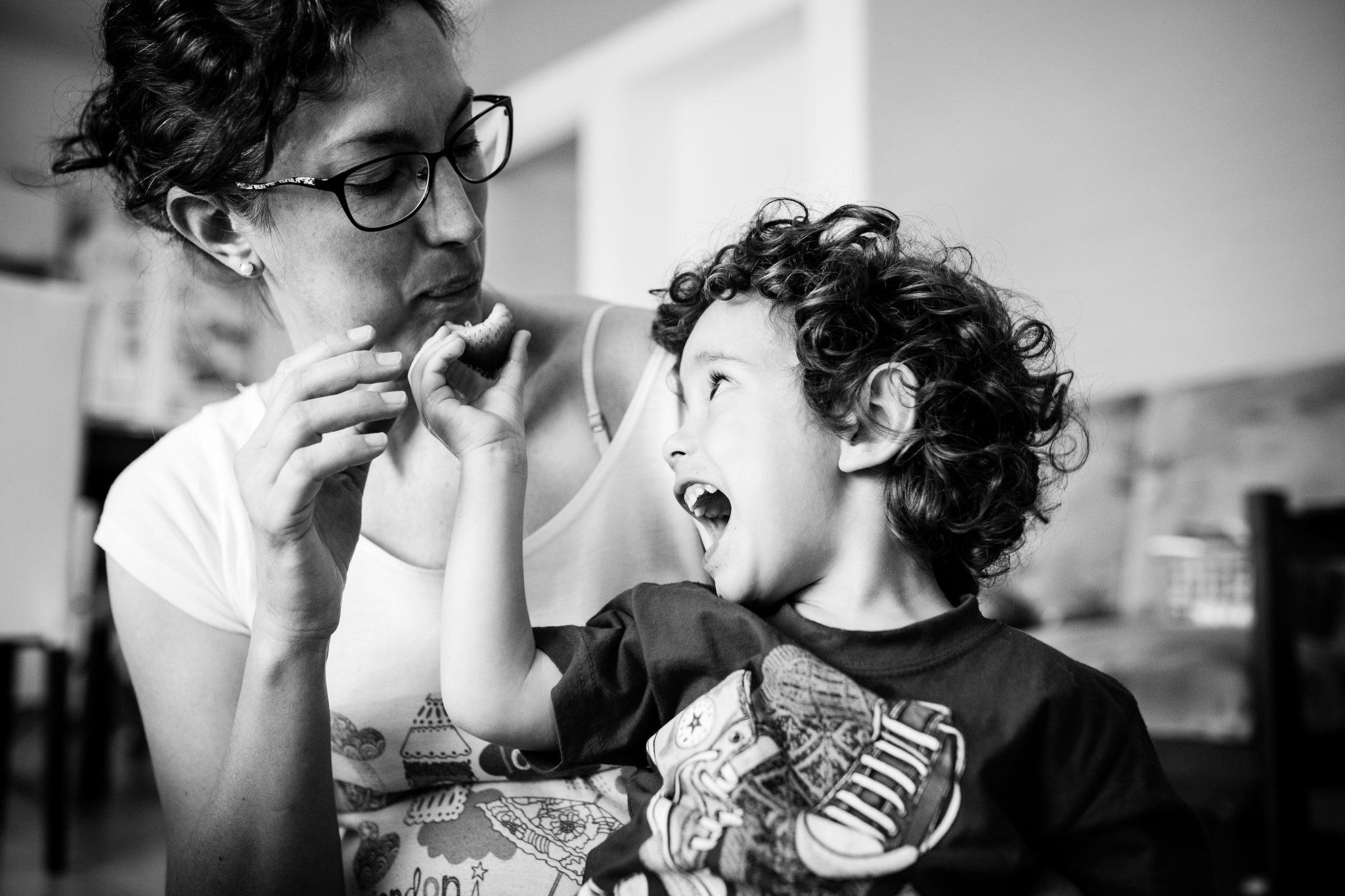 Toddler feeding his mom, giving her a strawberry while opening his mouth very big. Black and white photography.