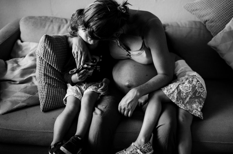 Pregnant mom sitting in the couch on her living room. She's with her too kids, kissing her boy, while hugging him. Her daughter is huging her. Picture in black and white. Amsterdam family photographer