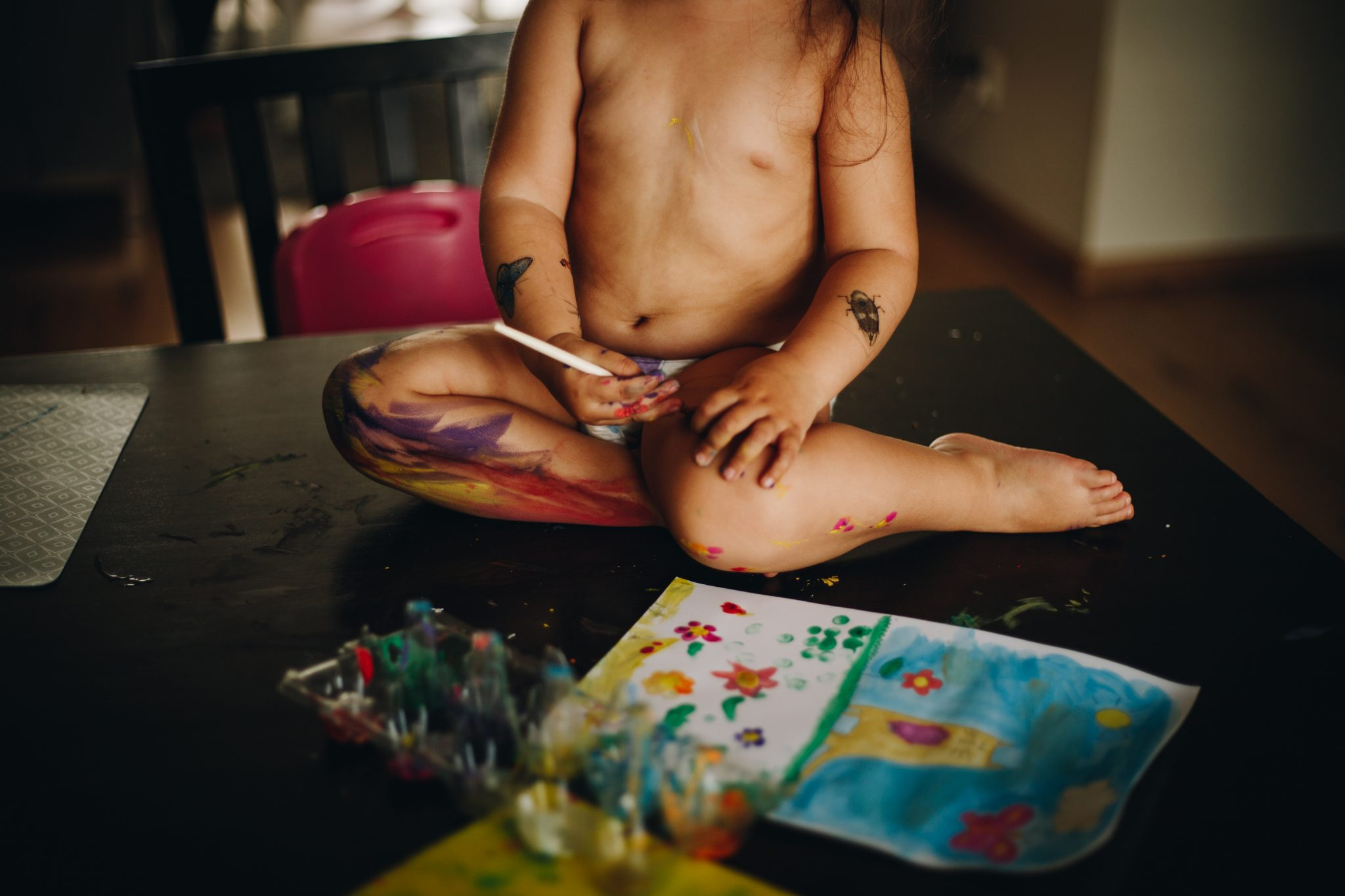 Girl painting herself with tempera sitting on the dinner table. Amsterdam.