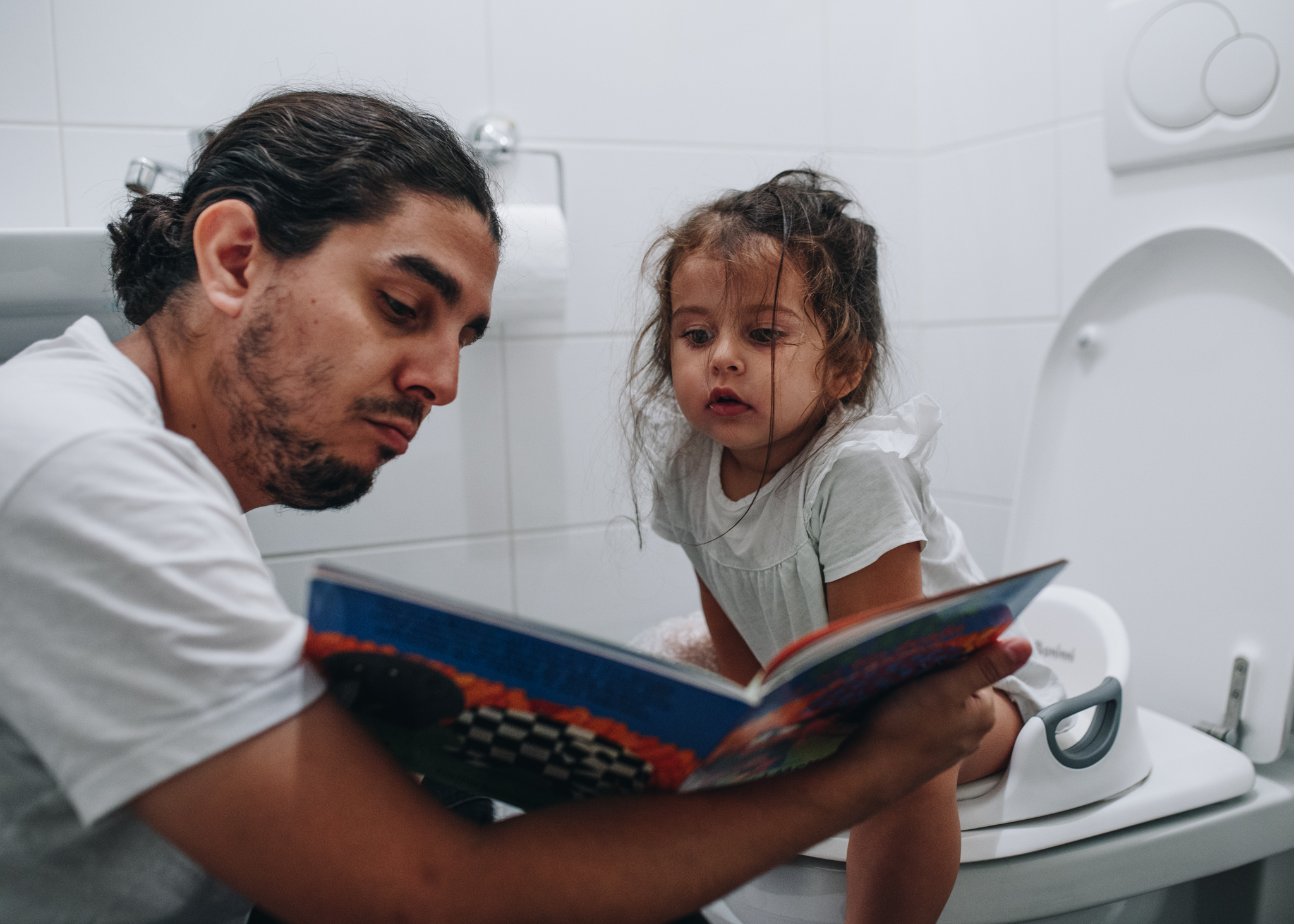 Dad reading a book to his daughter while she's sitting on the toilet