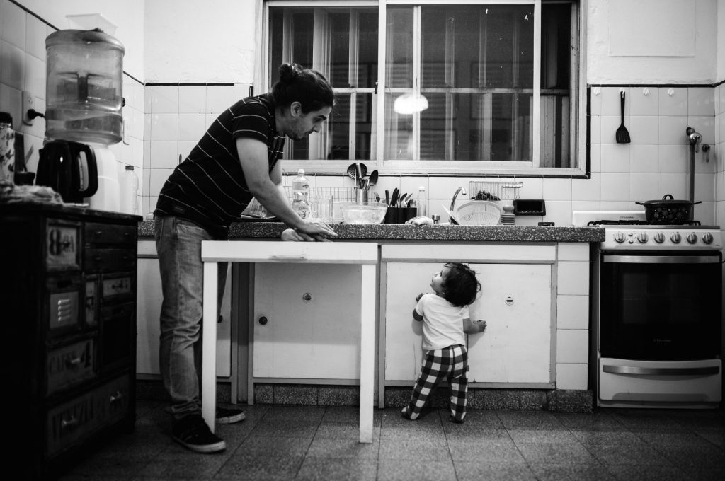 Dad cooking in the kitchen with his little toddler. Both standing, looking at each other, having a conversation. Picture in black and white. Day in the life, documentary family and baby photographer amsterdam, netherlands