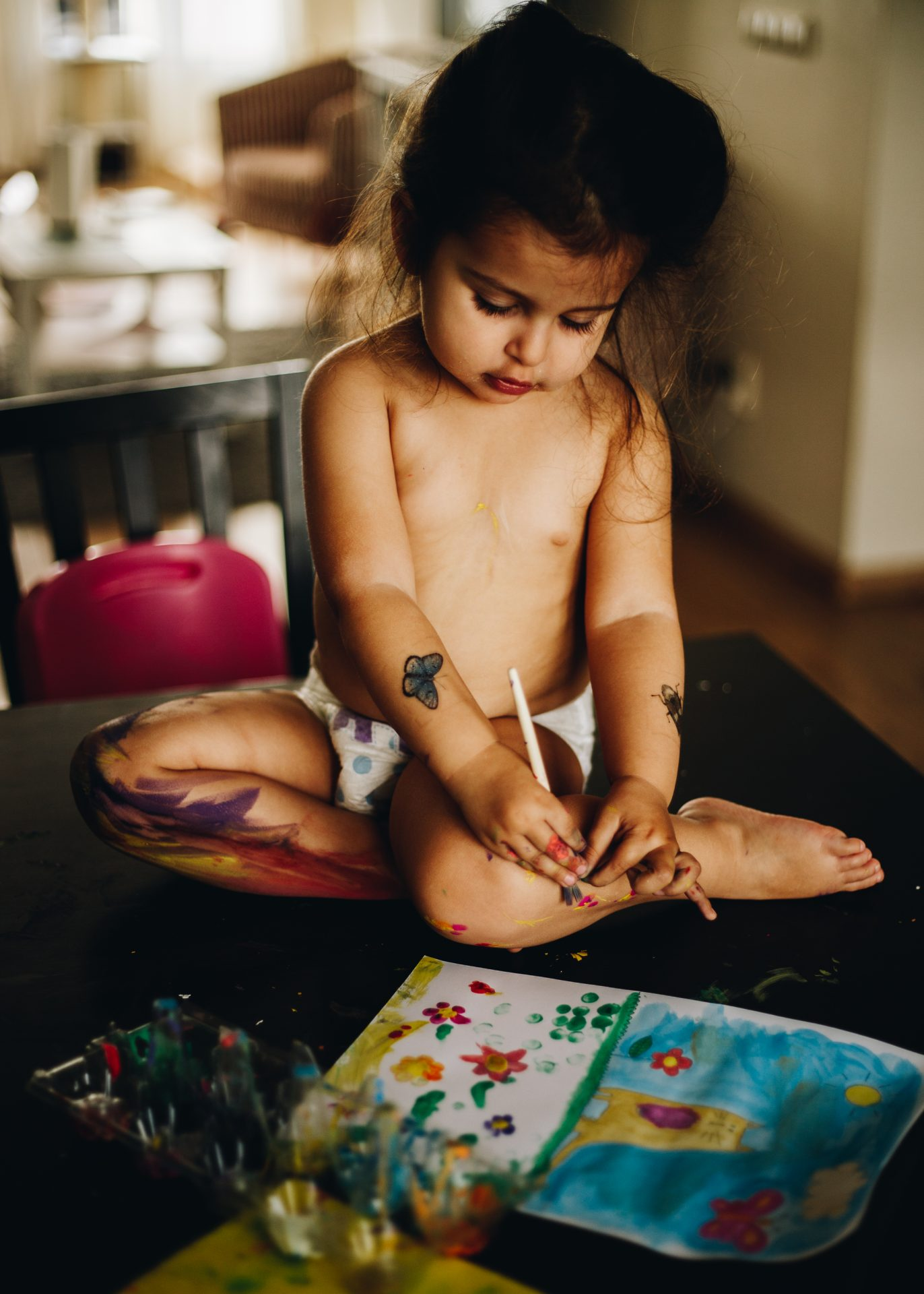 Toddler girl on the table painting her own legs with temperas. Natural style photographer. Amsterdam.