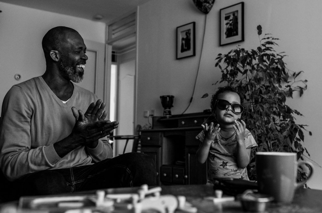 Black and White picture, toddler playing with his father sunglasses while dad's giving an applause and laughing. Documentary photoshoot in Amsterdam