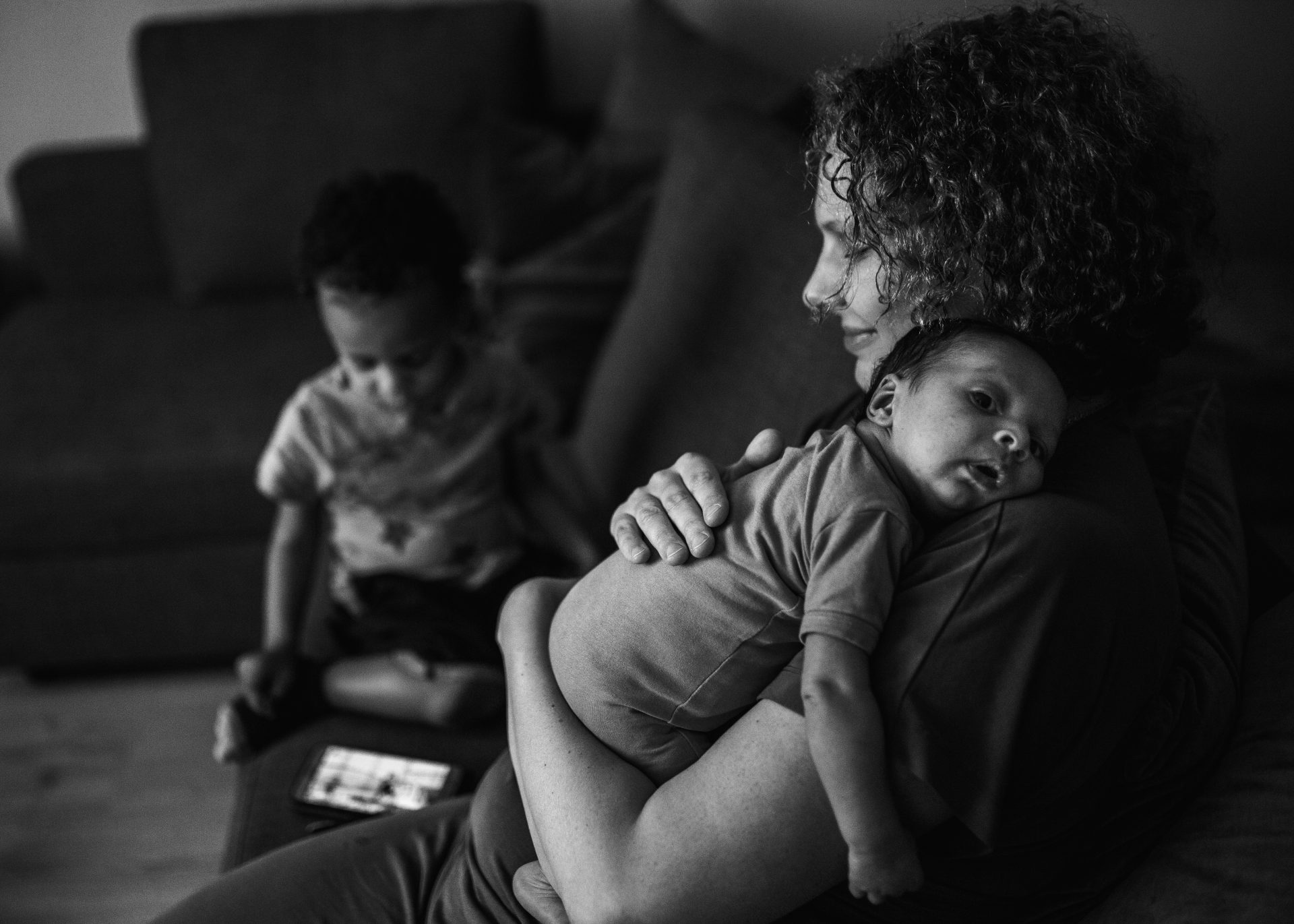 Black and white picture of mom holding her newborn in the livingroom with a calm smile, with her toddler next to her playing with a cellphone