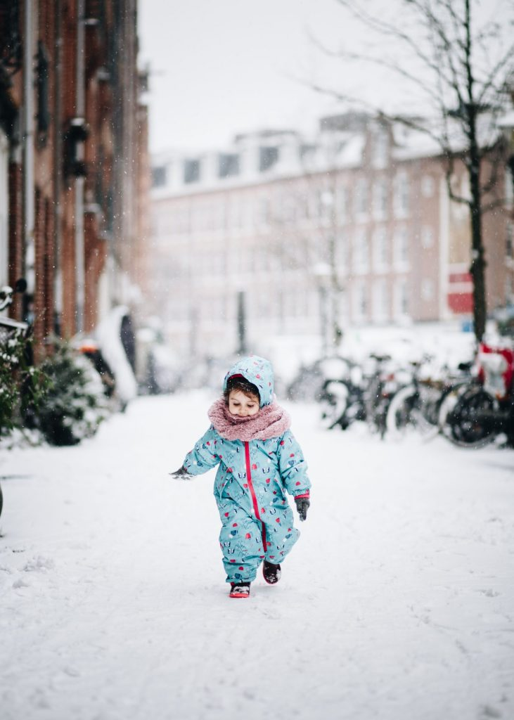 portrait of a girl runing in the snow on Amsterdam street