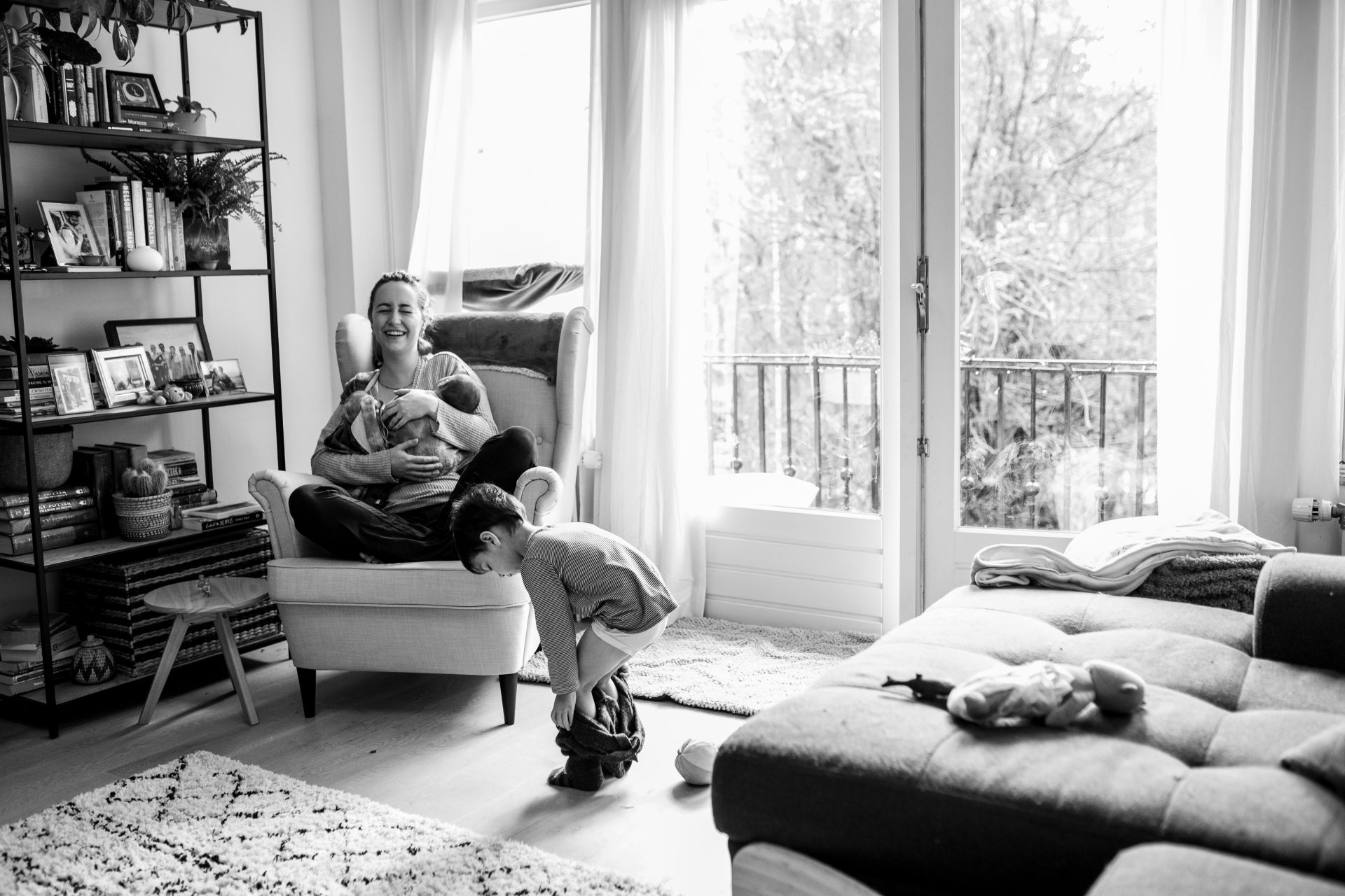 Mom holding her newborn while laughing hard because her older child is taking his own pants off. Black and white photo. In-home documentary session in Amsterdam.