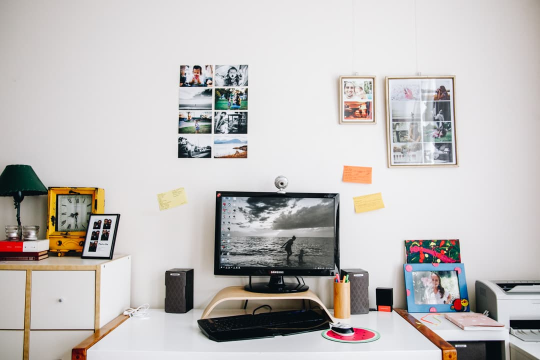 Computer desk displaying a photo of two girls runing on the beach (the photo is in black and white). Also, on the wall behind the screen you can see family photos hanging