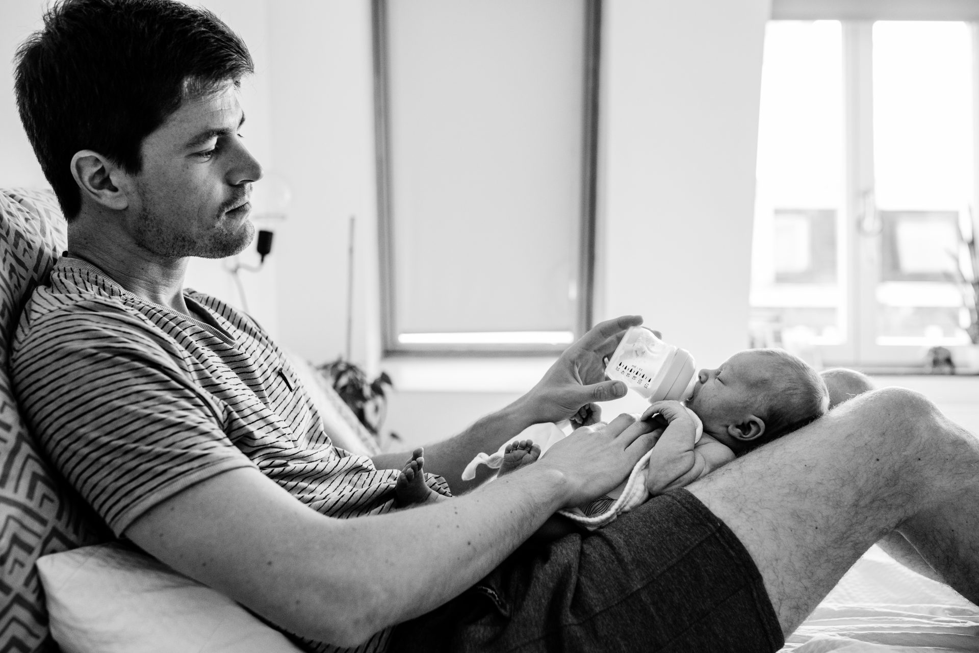 Dad feeding with bottle his newborn child, while baby is laying on his lap